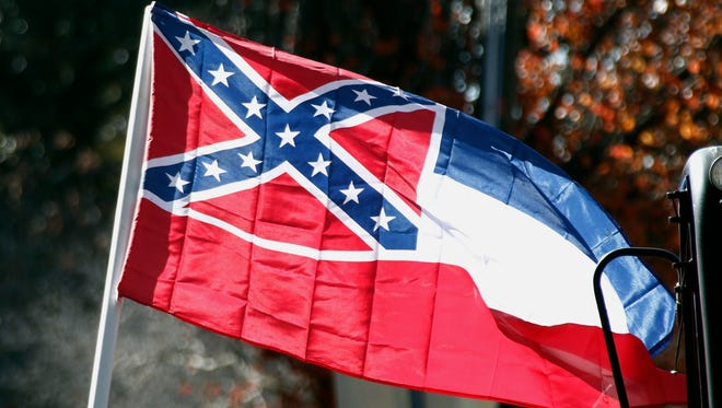FILE - In this Tuesday, Jan. 19, 2016 file photo, a state flag of Mississippi is unfurled by Sons of Confederate Veterans and other groups on the grounds of the state Capitol in Jackson, Miss.An effort to erase the Confederate battle emblem from the Mississippi flag is failing because sponsors didn't gather enough signatures to put an initiative on the 2018 ballot. (AP Photo/Rogelio V. Solis, File)