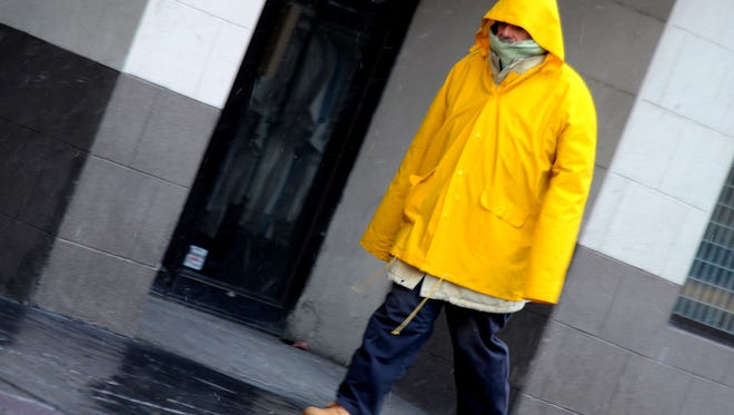 A file photo showing James Douglas, 65, of Reno wearing a rain coat as he walks along East Second Street near North Virginia Street. Forecaster say another storm wave is expected to drop rain and mountain snow.