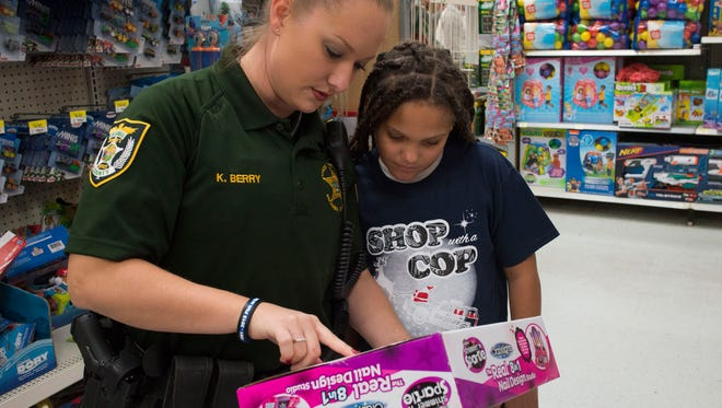 Escambia County Sheriff's Deputy Kristi Berry, left, and Savannah Bogan, right, shops for Christmas gifts at the Wal Mart on Hwy 29 Friday afternoon. ECSO School resource officers and select students took part in the annual Shop with a Cop event.
