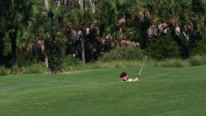 Jeanne McGinnis hits out of a bunker at Shadow Wood Country Club Preserve Course in south Fort Myers. Shadow Wood is one of many golf communities in Southwest Florida.