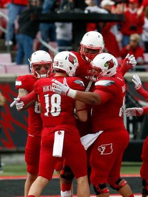 Louisville's Cole Hikutini (18) celebrates with teammates after scoring a touchdown. Nov. 7, 2015