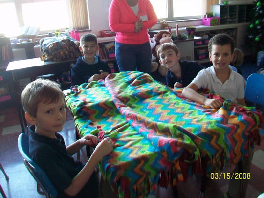 St. Margaret Mary Elementary School students Owen Hansen, from left, Mason Uhlenbrauck, Sean Osland and Max Osgood helped make tie blankets for The Family's Christmas Care program.