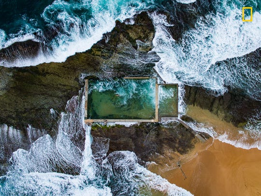 A rock pool in Sydney, Australia, at high tide. Waves crash over the edge. A long swimmer is undeterred.