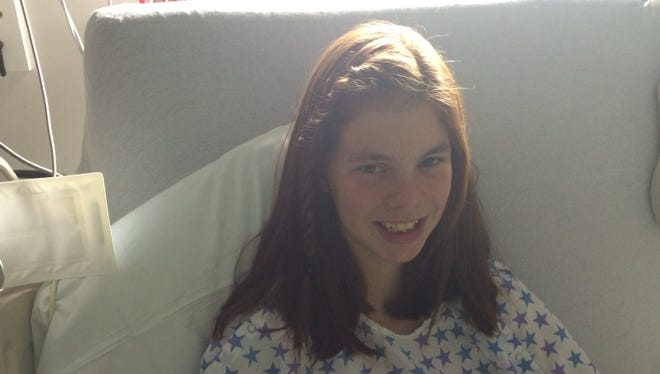 Megan Rowley sits on her hospital bed.
