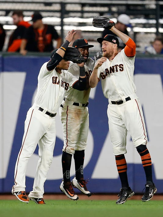 San Francisco Giants' Gorkys Hernandez, left, Denard Span, center, and Hunter Pence, right, celebrates the 8-6 victory against the Los Angeles Dodgers during the first inning of a baseball game, Tuesday, Sept. 12, 2017, in San Francisco. (AP Photo/Tony Avelar)