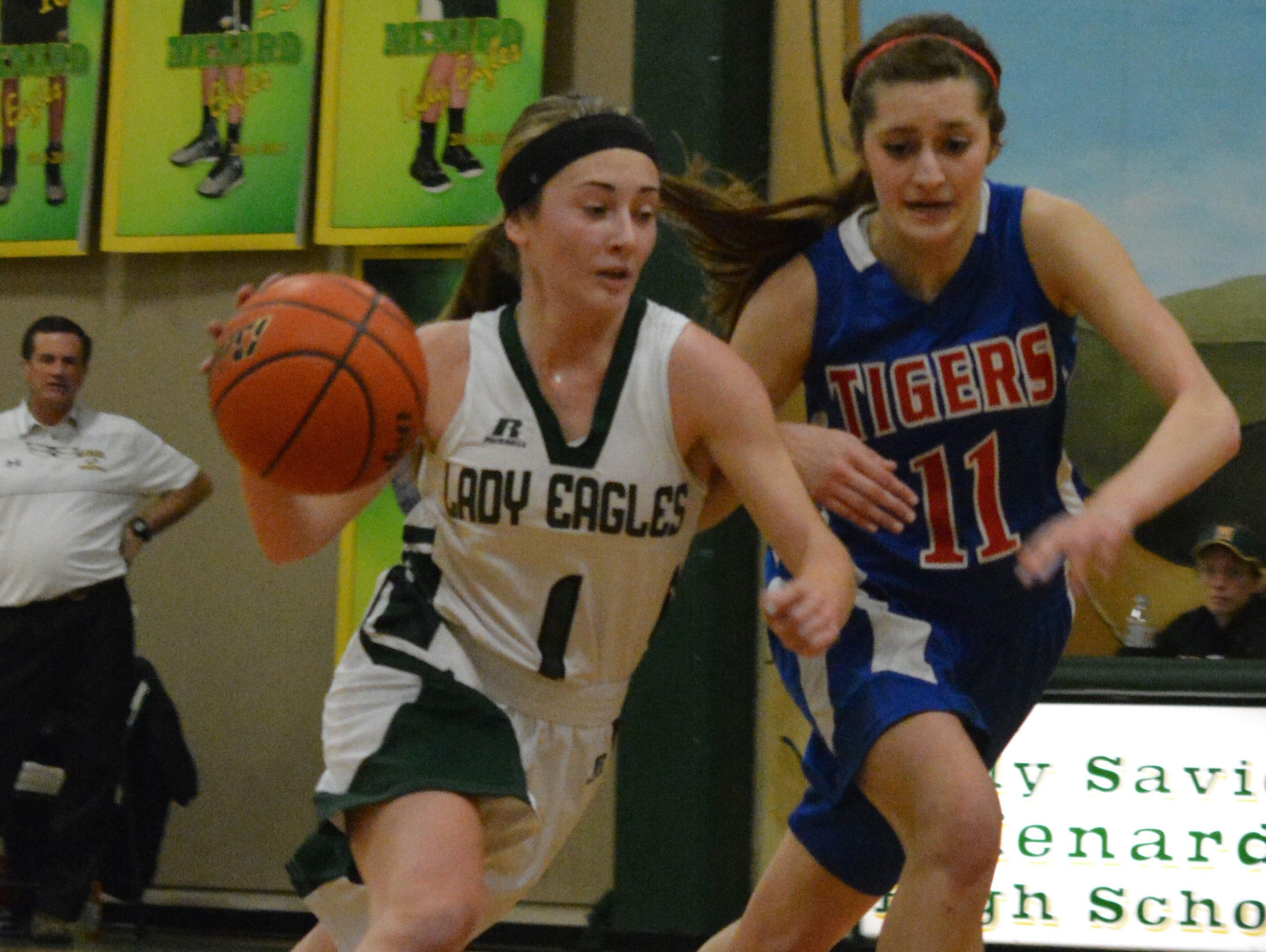 Menard's Morgan Woodard (1, left) drives to the basket against Lake Arthur's Kaitlyn Trahan (11, right) Tuesday, Feb. 24, 2015.