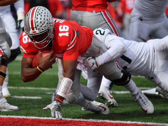 Quarterback J.T. Barrett #16 of the Ohio State Buckeyes scores on a four-yard touchdown run in the second quarter against the Michigan State Spartans at Ohio Stadium on November 11, 2017 in Columbus, Ohio.