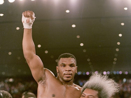 Boxing promoter Don King lifts heavyweight champion Mike Tyson after Tyson defeated Trevor Berbick in Las Vegas.