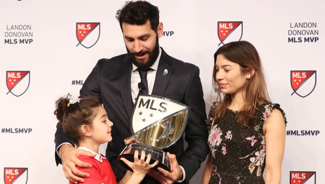 Portland Timbers midfielder Diego Valeri watches as his daughter, Connie, and his wife, Florencia, look at the Landon Donovan MVP Award he earned this year at Adidas America Headquarters.