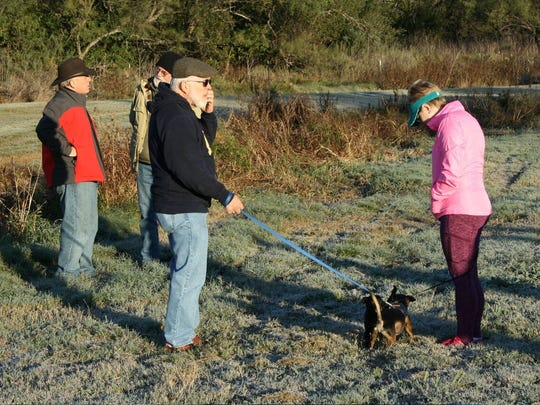 """Larry Wheeler and Gina Hockreiter, foreground, wait with their dogs, """"Lil Bit"""" and """"Sam"""" before heading out on the Mayor's Fall Hike 2016 on Saturday along Cedar Creek. In the background, Abilene Mayor Norm Archibald talks with a citizen about the vision for development along Cedar Creek."""