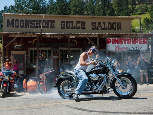 In this Aug. 2, 2014 photo Russ Kerstetter of Kansas City, Mo. uses his 2003 Harley-Davidson Fat Boy to perform a burnout in front of the Moonshine Gulch Saloon in Rochford, S.D.