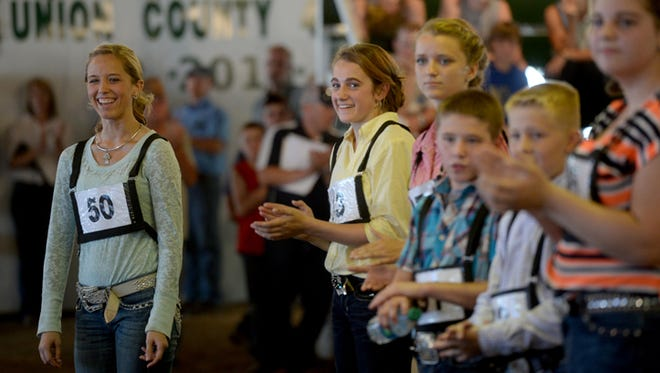 Payton Waltz, left, reacts after learning she is the winner of the round robin competition Thursday, July 23, 2015, during the Union County Fair in Liberty.