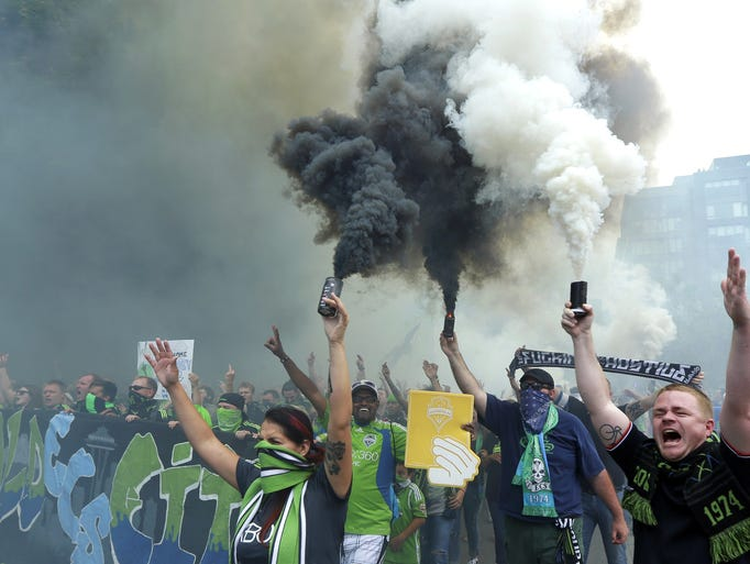 "Seattle Sounders supporters burn smoke devices during the traditional ""March to the Match"" before an MLS soccer match between Seattle Sounders FC and the Portland Timbers, Sunday, July 13, 2014, in Seattle. (AP Photo/Ted S. Warren)"