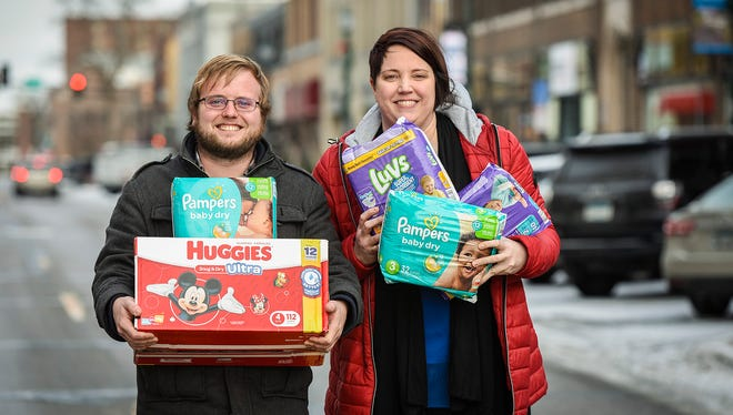 Justin Michael, volunteer organizer of Operation Baby New Year, and Donella Westphal, owner of Jules' Bistro, a diaper drop-off location,  show some of the donations Tuesday, Dec. 12, in downtown St. Cloud.