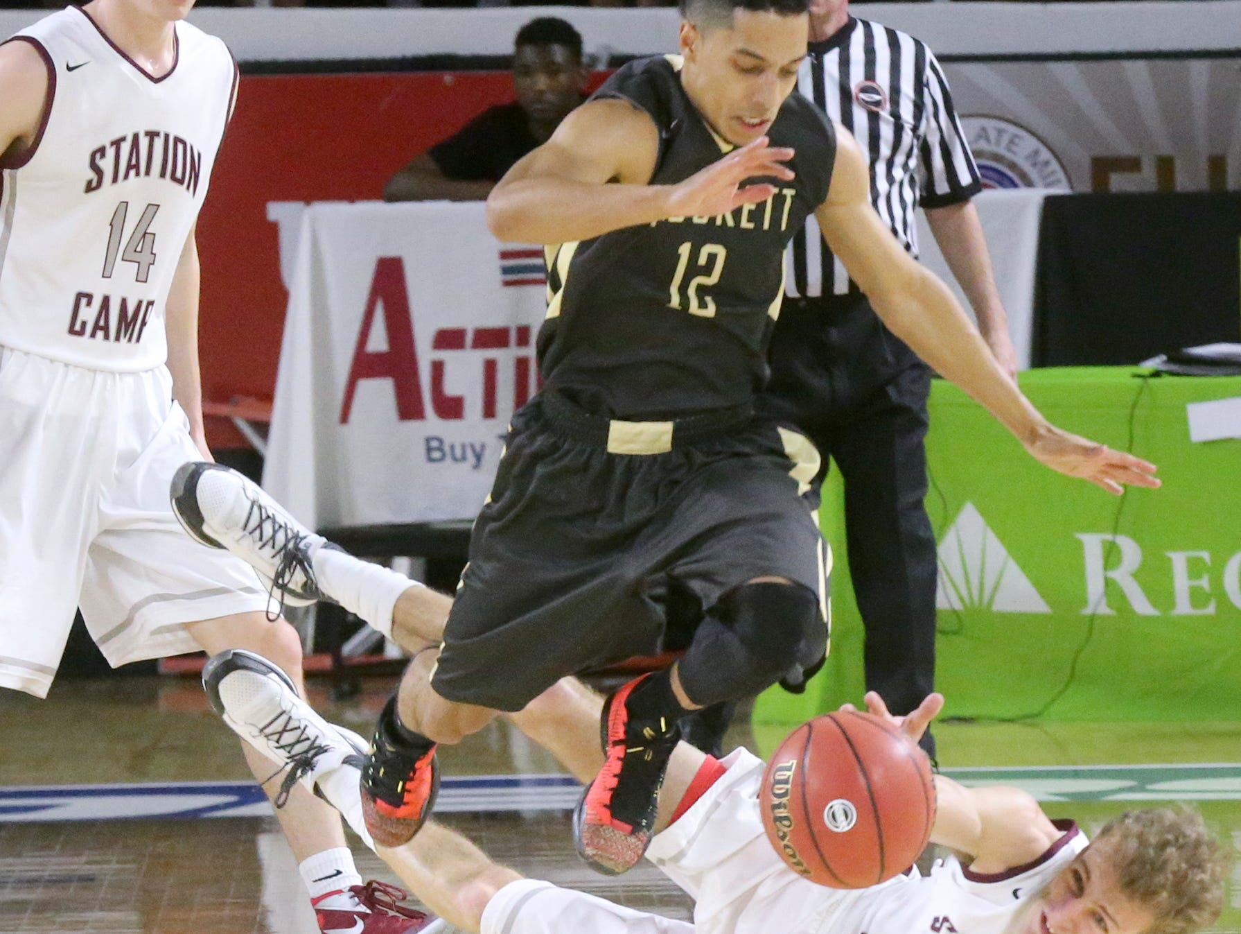"""Station Camp's Kody Eden (22) falls to the floor as he goes after a loose ball as David Crockett""""s Patrick Good (12) goes after the same ball during the Class AAA boys state quarterfinals at MTSU's Murphy Center Wednesday."""
