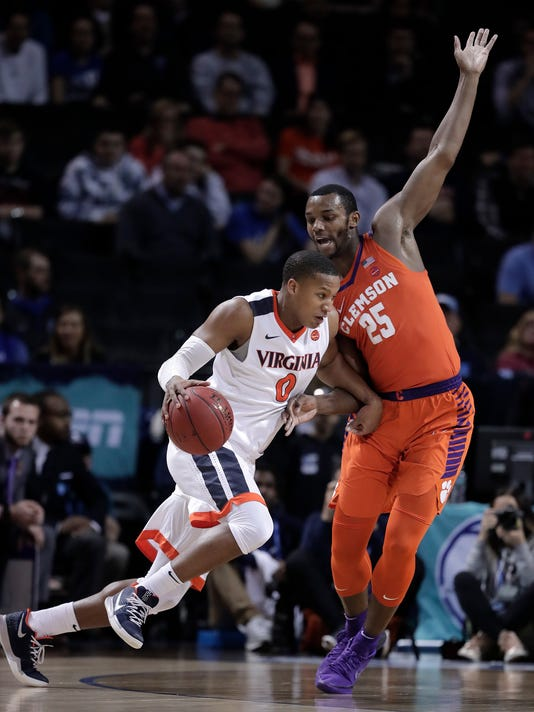 Virginia guard Devon Hall (0) drives against Clemson forward Aamir Simms (25) during the first half of an NCAA college basketball game in the Atlantic Coast Conference men's tournament semifinals Friday, March 9, 2018, in New York. (AP Photo/Julie Jacobson)