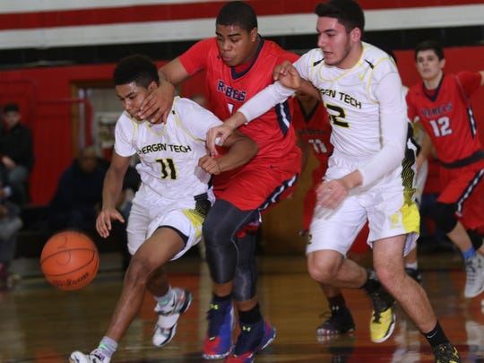 Marc Martinez of Bergen Tech keeps the ball away from Kevin Gibbs of Saddle River Day as Martinez gets help from team mate Firas Khansa.