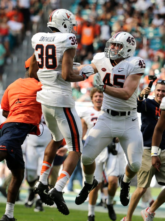 Virginia linebacker Charles Snowden (38) celebrates with linebacker Reed Kellam (45) after blocking a punt during the second half of an NCAA college football game against Miami, Saturday, Nov. 18, 2017, in Miami Gardens, Fla. Miami won 44-28. (AP Photo/Lynne Sladky)