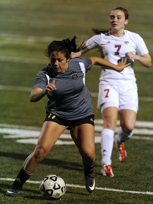 Thomas Metthe/Reporter-News   Abilene High's Riley Cranford (11) runs the ball down the field past Cooper's Courtney Osborne (7) during the second half of the Lady Eagles' 3-1 win in the opening day of the West Texas Invitational Tournament on Thursday, Jan. 7, 2016, at Shotwell Stadium.