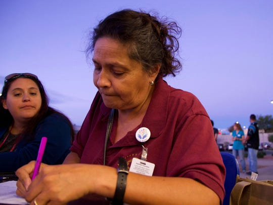Volunteer and Las Cruces Public Schools social worker Yoli Silva sits at a registration table outside Old Navy to check-in families during the 31st annual Dress the Child event earlier this month.