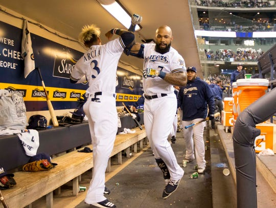 Orlando Arcia and Eric Thames celebrate in the dugout after Thames hit a 2-run homer against the Cincinnati Reds.