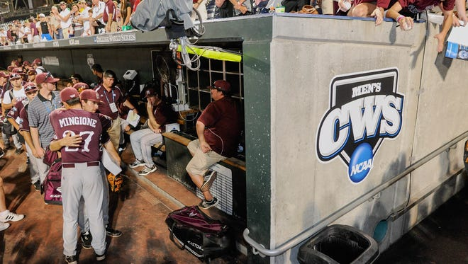 Mississippi State assistant coach Nick Mingione (27) hugs a player as coach John Cohen sits in the dugout, second right, after losing to UCLA 8-0 in Game 2 of the NCAA College World Series baseball finals, Tuesday, June 25, 2013, in Omaha, Neb. UCLA won the championship.