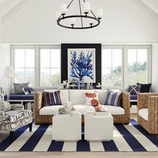 Coral in indigo is a stunning focal point in this airy, eclectic design from Williams-Sonoma Home, which teams a modern fern-patterned upholstery, woven chairs, white sofa and a wide-striped rug. The giclee prints on archival paper are  framed in painted white pine.