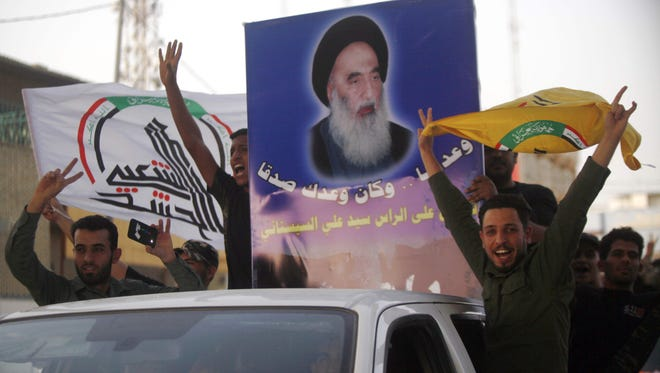 "Iraqis flash the sign for victory next to a portrait of Shiite cleric Grand Ayatollah Ali al-Sistani as they celebrate in the streets of the holy city of Najaf on July 11, 2017 a day after the government's announcement of the ""liberation"" of the embattled city of Mosul."