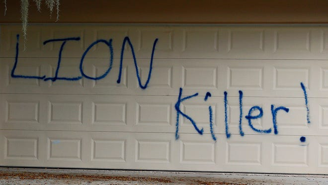 """Private Investigator for the Palmer family, Walter Zalisko, of Global Investigative group in Fort Myers walks out of the home Tuesday, Aug. 4, 2015, at the Marco Island home of dentist Walter J. Palmer. Zalisko said no vandalism was found inside. The home was discovered vandalized with the worlds """"LION Killer!"""" and littered with pigs feet drenched in hot sauce. Palmer, a Minnesota resident, is wanted in the killing of Zimbabwe's famous lion, Cecil, a lion who drew thousands of tourists and dollars annually."""
