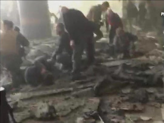 FILE - In this Tuesday, March 22, 2016 image made from video provided by RTL Belgium, people receive treatment in the debris-strewn terminal at Brussels Airport after a series of explosions. Across the globe, terrorist attacks flared at a relentless pace throughout the year. Among the many high-profile attacks were those that targeted airports in Brussels and Istanbul, a park teeming with families and children in Pakistan, and the seafront boulevard in Nice, France, where 86 people were killed when a truck plowed through a Bastille Day celebration. In Iraq alone, many hundreds of civilians were killed in repeated bombings.