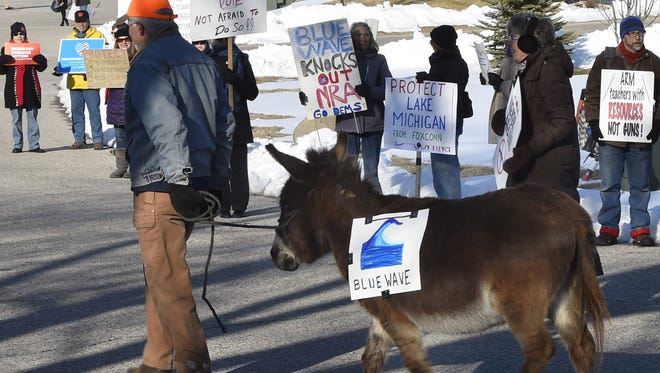 Dewey the donkey and owner Tony Nellis find a spot along the roadway on Nautical Way in Sturgeon Bay with Indivisible Door County group protesting Gov. Scott Walker's platform. Walker was attending the Lincoln Day Dinner hosted by the Republican Party of Door County at the Sturgeon Bay Yacht Club on Saturday, April 7, 2018.