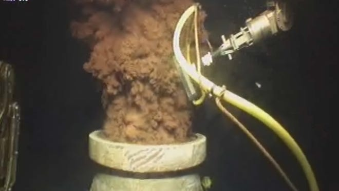 In this July 12, 2010 image from video made available by BP, oil flows out of the top of the transition spool, which was placed into the gushing wellhead and will house the new containment cap, at the site of the Deepwater Horizon oil spill in the Gulf of Mexico.