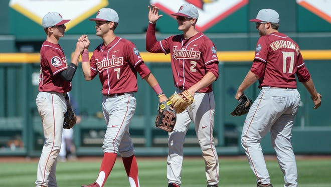Florida State outfielders Jackson Lueck (2) and Steven Wells, Jr. (7) lead the celebration after the Seminoles win over Cal State Fullerton at TD Ameritrade Park in Omaha.