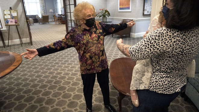 Gloria Winston, 94, left, opens her arms wide to get a hug from her great-niece Wensday Greenbaum, right, and her 5-year-old great-great-niece Cordelia Cappelano on Thursday at Laurelmead Cooperative retirement community in Providence, Rhode Island.