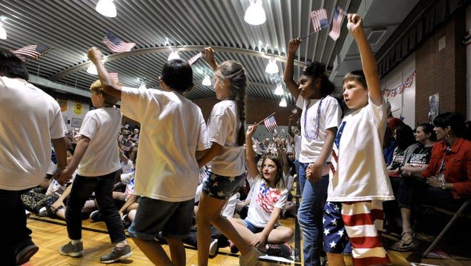 """Students wave small American flags and march between their classmates, parents, and faculty during the annual Dyess Elementary School performance of """"I Love America"""". The patriotic program featured the fifth-grade class and was briefly interrupted by a tornado warning."""