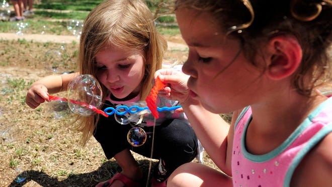 Jensen Dobbs and Alli Williams blow soap bubbles during the 2015 Healthy Families San Angelo Children's Fair.