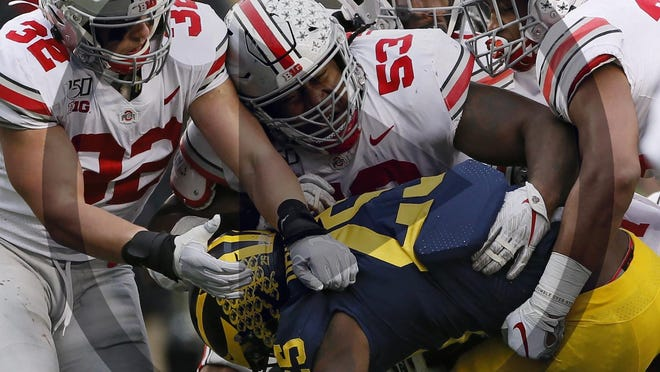This file photo shows a plethora of Ohio State Buckeyes, including, linebacker Tuf Borland (32), defensive tackle Davon Hamilton (53), linebacker Malik Harrison (39) and defensive lineman Robert Landers (67) team up to stop Michigan Wolverines running back Hassan Haskins (25) during the fourth quarter of the NCAA football game at Michigan Stadium in Ann Arbor, Mich. on Saturday, Nov. 30, 2019.