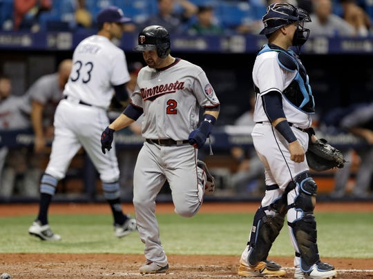Minnesota Twins' Brian Dozier (2) scores in front of Tampa Bay Rays catcher Jesus Sucre on a throwing error by Rays relief pitcher Steve Cishek (33) during the seventh inning of a baseball game Wednesday, Sept. 6, 2017, in St. Petersburg, Fla. (AP Photo/Chris O'Meara)