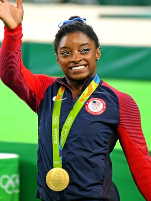 Simone Biles celebrates winning the all-around gold medal.