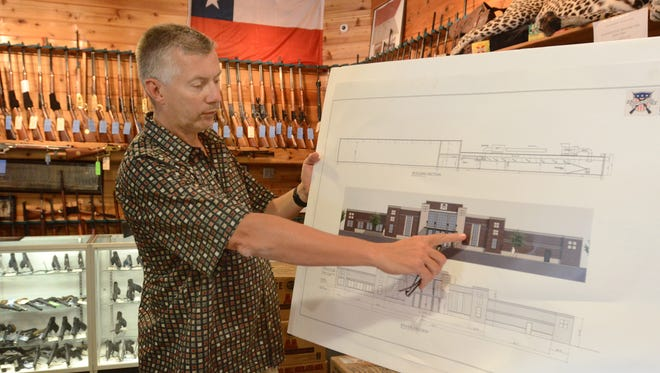 Ed Swadish, owner of Huron Valley Guns, shows off plans for a new state-of-the-art firearms facility he initially planned to build in Milford Township. but has now decided to carry out his plans in Lyon Township.