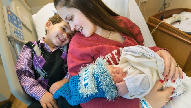 From left: Mason Banks, age 3, cuddles with his mother Erica Callender and Madden Banks, the first 2017 baby born in a York County hospital.