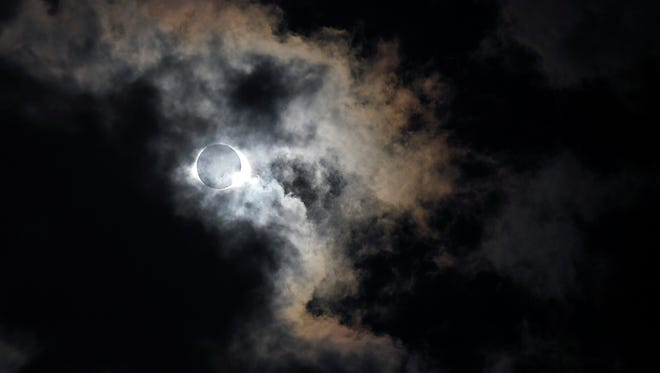 Eclipse shows through the clouds at Nashville's eclipse-viewing party at First Tennessee Park Monday, Aug. 21, 2017 in Nashville, Tenn.