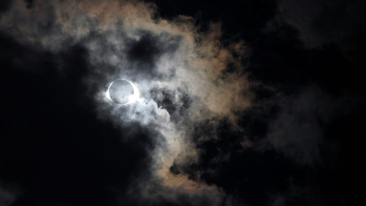 Eclipse shows through the clouds at Nashville's eclipse-viewing