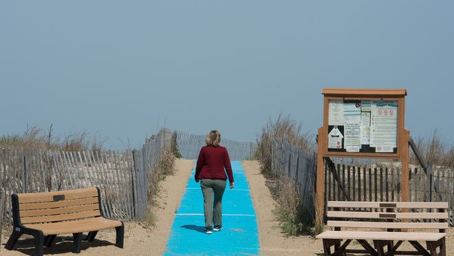 Margaret Moors of Phoenix, Md., who also owns a home in Dewey Beach, walks on the blue mats leading up to the beach on Dagsworthy Street in Dewey Beach.  Dewey Beach is expanding the blue mat program to all the dunes.