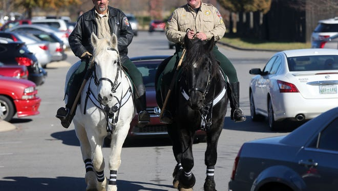 Sgt. Jon Levi, right, riding Lushy, and Deputy Kerry Nelson, on Lenny, of the Rutherford County Sheriff's Mounted Patrol ride through the parking lot at The Avenue Murfreesboro shopping center during Black Friday.
