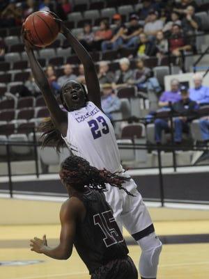 Abilene Christian's Suzzy Dimba (23) drives for a shot against McMurry's Dakkia Morris during an exhibition game Nov. 7 at Moody Coliseum.