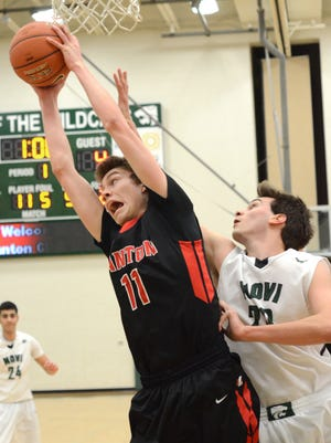 Canton's Logan Ryan (No. 11) grabs a rebound in front of Novi's Jay Duarte during Monday's Class A district boys basketball contest.