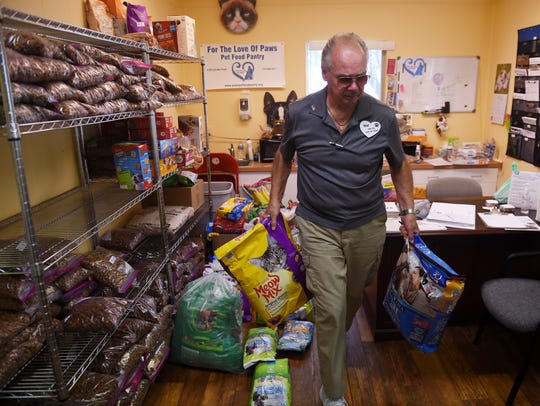 Ted Pankiewicz moves bags of dog and cat food around