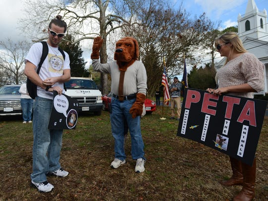 Jerry Barker, from left, Raymond Barker and Kristin Kulynych prepare to march with other protesters during a rally against PETA after two PETA workers took a family dog and later admitted to euthanizing it.