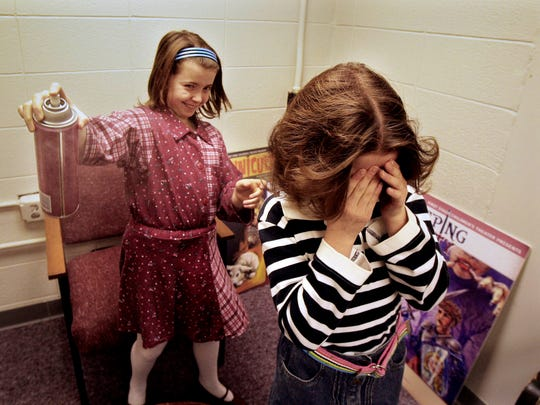 "Sydney Salter (left) applies a little hair spray to her twin sister Alex's hair as part of preparations for a 2009 performance of ""The Best Christmas Pageant Ever"" by First Stage."